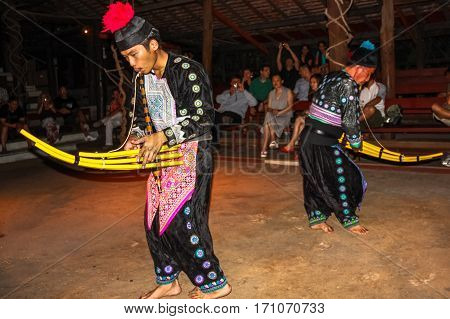 Chiang Mai, Thailand - July 24, 2011: musicians dressed in traditional dress playing during folk show at Kantoke Palace in Chiang Mai.