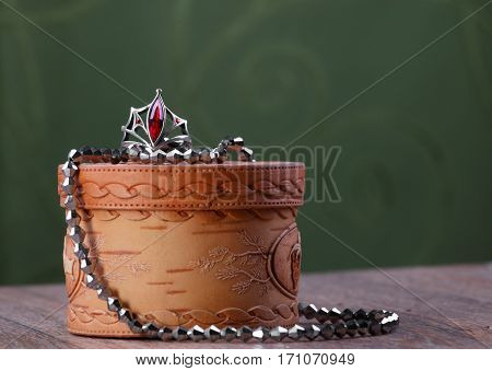 metal beads and a ring with a red stone on small closed birch bark casket on green fabric background