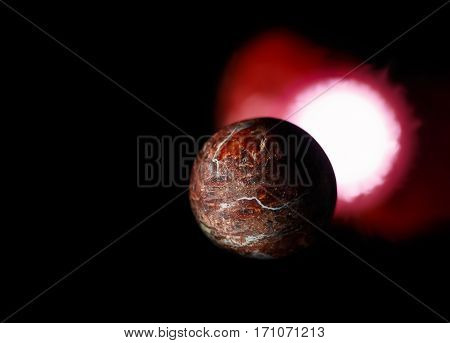 rock planet and red sun on black background. In outer space theme.
