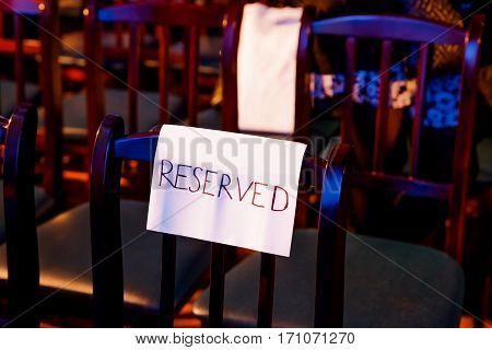 One wooden theater seat with the handwritten reserved sign. Color light.