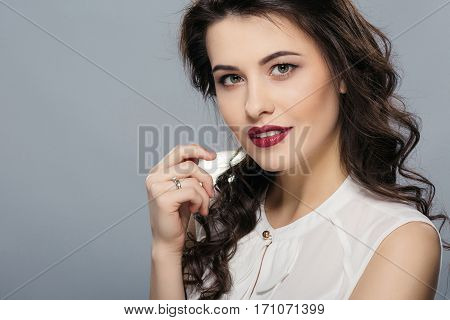 Darkhaired woman with long curly hair, big eyes and red lips wearing white shirt looking at camera, holding hand near face, gray studio background, copy space.
