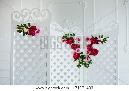 White delicate decorative wood panel in classical interior. Boudoir wedding room. Retro folding screen with flowers. Vintage ornate carved folding screen