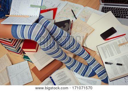 Teen in knee-height striped socks is preparing for school, college or university exams