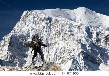 View of south rock face of mount Annapurna 3 III Annapurna range and hiker Annapurna circuit trekking trail Nepal