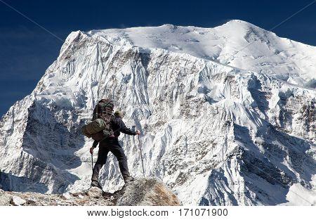 View of south rock face of mount Annapurna 3 III Annapurna range and hiker Annapurna circuit trekking trail Nepal