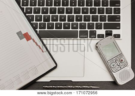 Laptop, diary or planner and a dictaphone on the student's or journalist's black wooden table