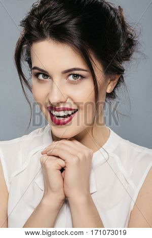 Darkhaired woman with dark hair, big eyes and red lips wearing white shirt looking at camera and smiling, portrait, gray studio background, make up model.