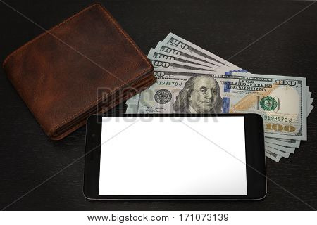 Still life after receipt of the fee - some US dollar notes, leather wallet and a cell phone on the black wooden table