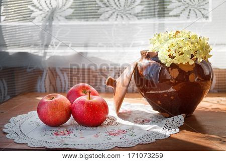 three apples and old cracked clay pot with flower in sunlight on a wooden surface