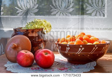 apples plate with yellow raspberries and old cracked clay pot with flower in sunlight on a wooden surface
