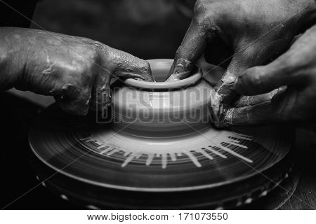 hands working with clay in blackly white color