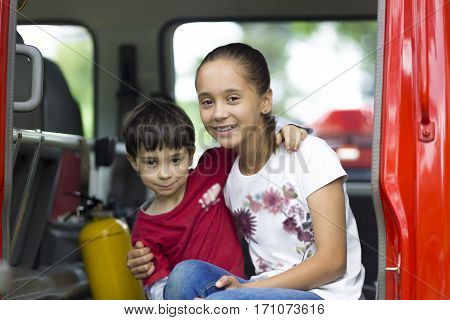 Happy Girl And Boy In Firefighter Car