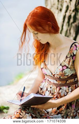 Young redhead woman writing in summer park