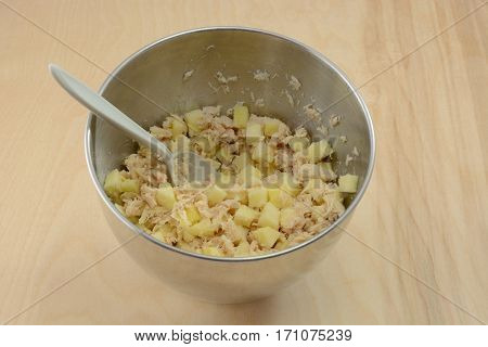 Mixing together apple cubes and albacore tuna fish in stainless steel mixing bowl with plastic spoon