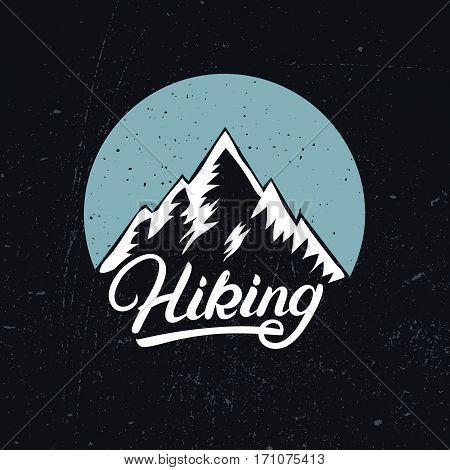 Hiking hand written lettering logo, label, badge, emblem with mountains. Adventure symbol on black background. Grunge texture. Vector illustration.