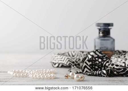 Woman Scarf On Table With Parfume And Pearl Bijouterie