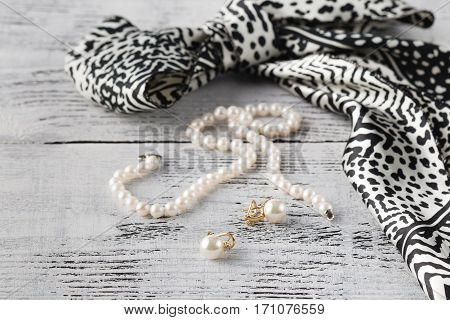bijouterie pearl on white wooden table with scarf
