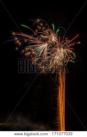 Firework explosions in dark and starry sky