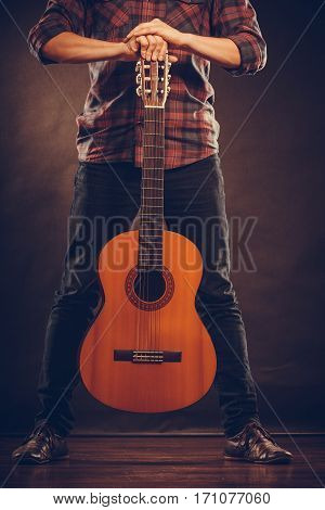 Hobby music concept. Person is standing with guitar. Man is holding the instrument.