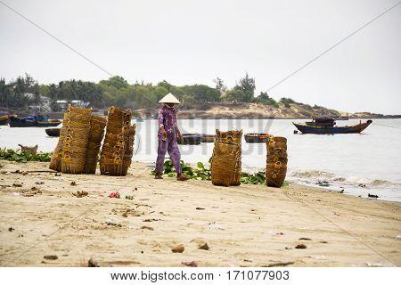 Woman Washing Baskets On Fish Sauce Production, Mui Ne, Vietnam