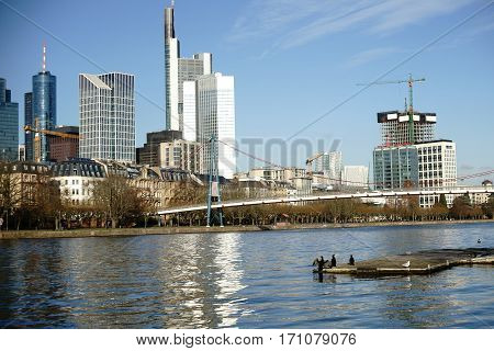 The skyline of the banking district at the Holbeinsteg-Bridge in Frankfurt behind the River Main.