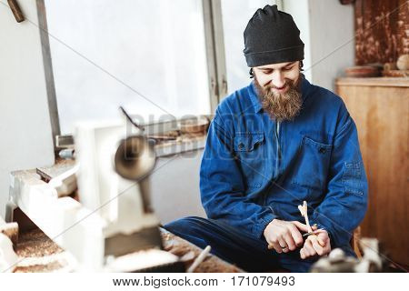 Man with a beard wearing blue jeans suit and black hat carving woo and looking at wooden spoon, woodcarving instruments on table, portrait.