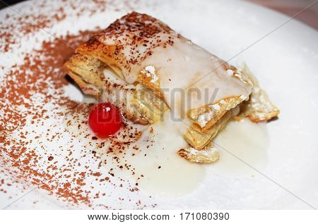 Napoleon cake with cherry on the white plate