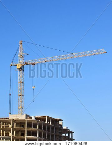 Construction crane over blue sky at the construction site