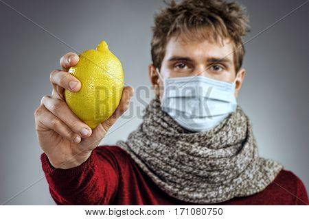 Sick man holding lemon. Photo of man wears protective mask against infectious diseases and flu. Healthcare concept