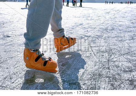 male legs with skates ice skating on the lake