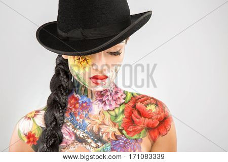 Beautiful girl with dark long hair wearing black hat, body art paintings on neck, shoulders and face, painting flowers, make up model, closed eyes.