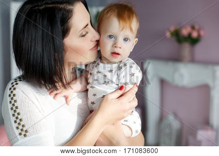 Happy young mother,a woman with black hair,red nail Polish,light makeup,dressed in a white blouse,holding her small son,a boy with red hair and blue eyes,dressed in a white t-shirt with grey stars,a portrait in the living room with pink walls