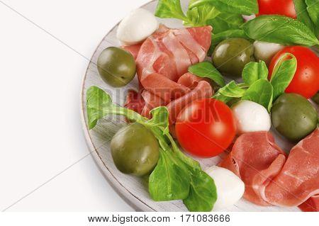 Prosciutto mozzarella cherry tomatoes lettuce and olives - Italian appetizer.