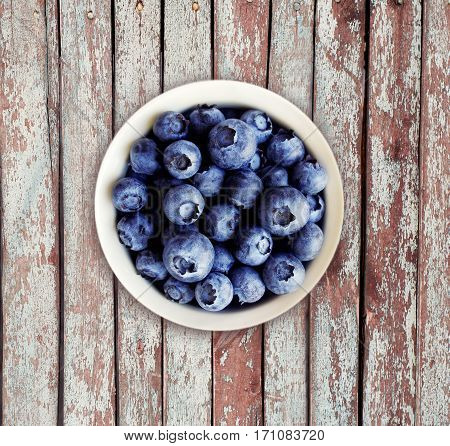 Blueberries in a white ceramic bowl. Top view. Ripe and tasty blueberries on a wooden background.