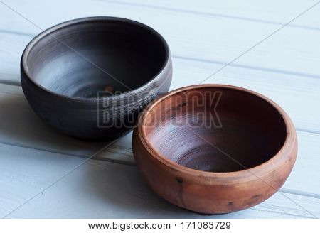 Composition from ceramic bowls on wooden background