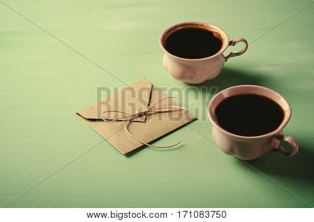 Love letter, envelope and two pink cups of coffee. Valentines card. Horizontal, toned