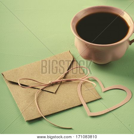 Love letter, envelope with paper heart and pink cup of coffee. Valentines card. Square, toned