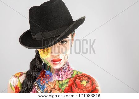 Gorgeous girl with dark long hair wearing black hat, body art paintings on neck, shoulders and face, painting flowers, make up model, looking at camera, copy space.