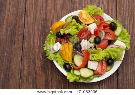fresh vegetable salad isolated on white background with tomatoes, black olives and greens close