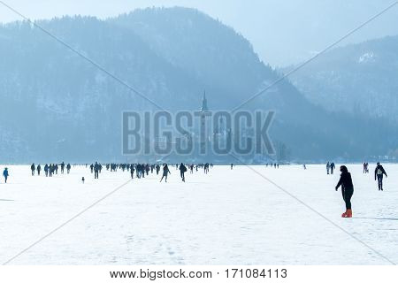 frozen lake Bled unique phenomenon many people on ice walking
