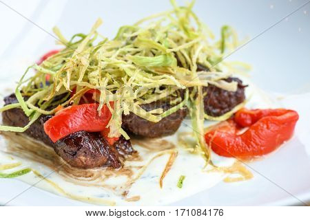 Beef medallions with greens, fry, red boiled pepper and white cheese sauce on a white plate, brown bread, restaurant table, close up