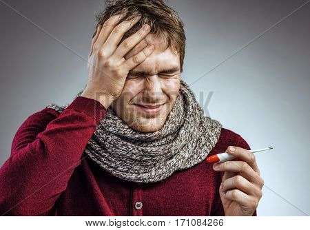 Man suffering from severe headache. Photo of sick man in scarf holding his head with his hands and feels anguish