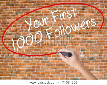 Woman Hand Writing Your First 1,000 Followers  With Black Marker On Visual Screen