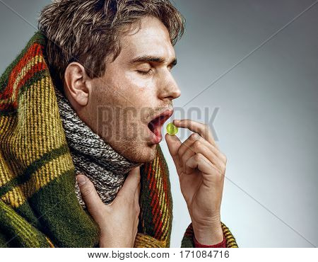 Man with open mouth take pill for throat. Photo of sick man wrapped in blanket on grey background
