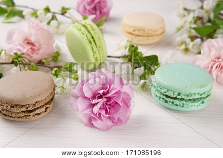 French macaroons. Turquoise chocolate and green colors. Spring concept. Background with flowers and macaroons.
