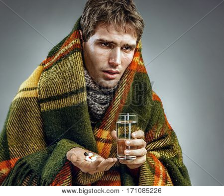 Sick man with tired face expression taking medicine tablets. Photo of man suffering common cold and winter flu virus.