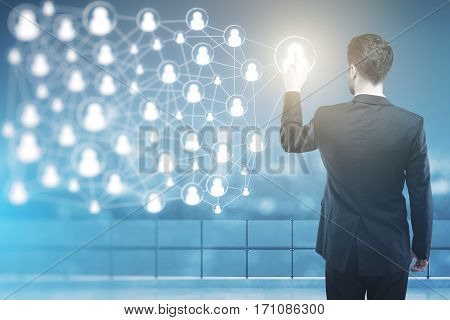 Back view of businessman in suit pointing at abstract connected people icons at night. HR and network concept