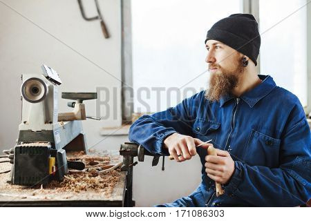 Man with a beard wearing blue jeans suit and black hat sitting on working place with wooden spoon and looking left, woodcarving instruments on table.
