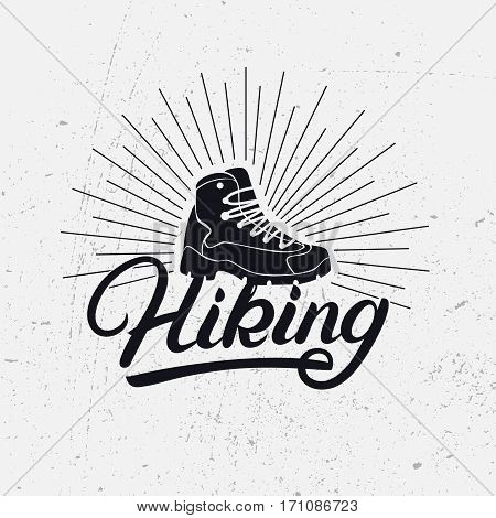 Hiking hand written lettering logo, label, badge, emblem with boot. Adventure symbol on gray background. Grunge texture. Vector illustration.