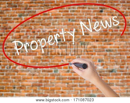 Woman Hand Writing Property News With Black Marker On Visual Screen